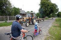 Bicycling Polish dad and daughter stop for tractor and cart to pass by. Zawady Central Poland