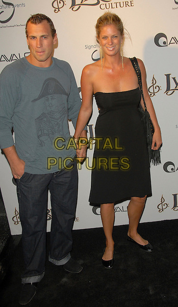 JARRET STOHL & RACHEL HUNTER .The Lyric Culture Launch Party held at Avalon in Hollywood, California, USA. .May 10th, 2007.full length jeans denim rolled up turned blue top holding hands couple black strapless dress tassels bag purse .CAP/DVS.©Debbie VanStory/Capital Pictures