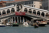 Crowds of tourists looking on to the Grand Canal from the Rialto bridge. Venice, Italy.