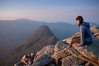 Female hiker on summit of Glyder Fach with Tryfan in background, Snowdonia national park, Wales