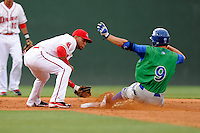 Second baseman Yoan Moncada (24) of the Greenville Drive applies the late stage as Brandon Downes (9) of the Lexington Legends slides in with a double on Monday, May 18, 2015, at Fluor Field at the West End in Greenville, South Carolina. Moncada, a 19-year-old prospect from Cuba, made his professional debut tonight in the Red Sox organization. (Tom Priddy/Four Seam Images)