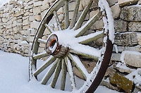 An old wooden wagon wheel covered in fresh snow. Fayette State Park, Garden Peninsula.