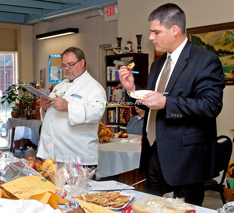 NAUGATUCK CT- OCTOBER 18 2011 -101812DA02- Naugatuck Mayor Robert A. Mezzo examines an peice apple pie before tasting it to judge the apple pie or apple cake contest along with Ron Pascoe, director of dining for the Village at East Farms in Waterbury. The event was held at the Naugatuck Senior Center during the Apple Harvest Festival on Thursday.Darlene Douty Republican-American