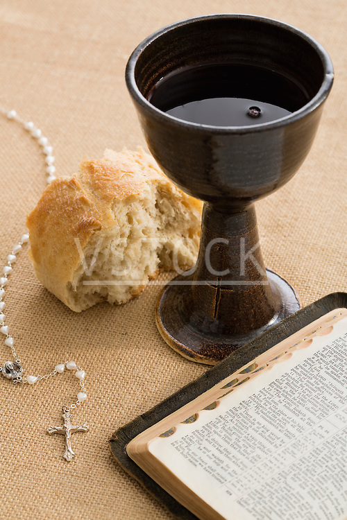 Holy Bible, pearl rosary beads, piece of bread and chalice with wine