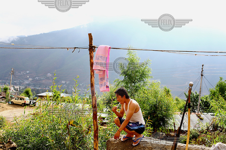 A man brushes his teeth outside his hut in the kala bazzar slum.