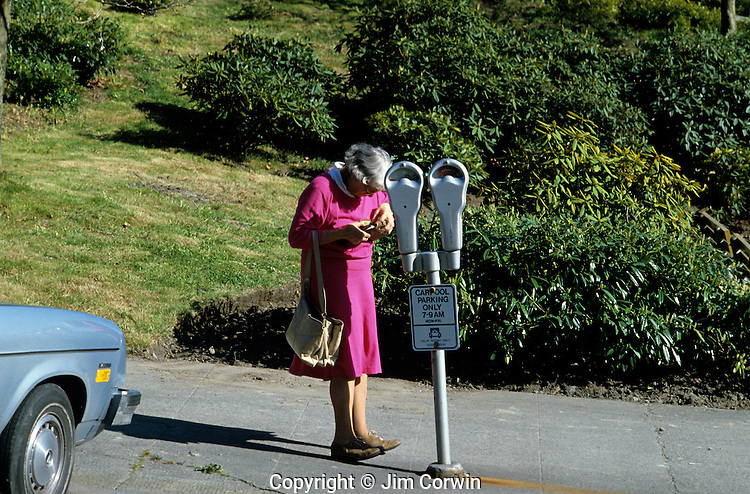 Older woman getting coins out of her purse to pay parking meter