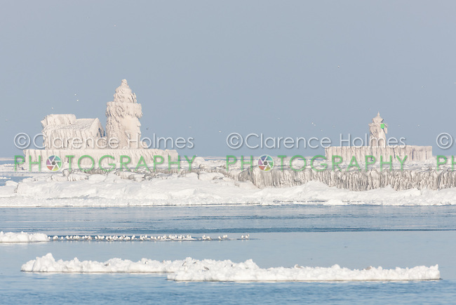 The Cleveland Harbor West and East Pierhead Lights covered by frozen layers of ice.  The lighthouses were encased in ice by crashing waves in frigid air temperatures during mid-December.