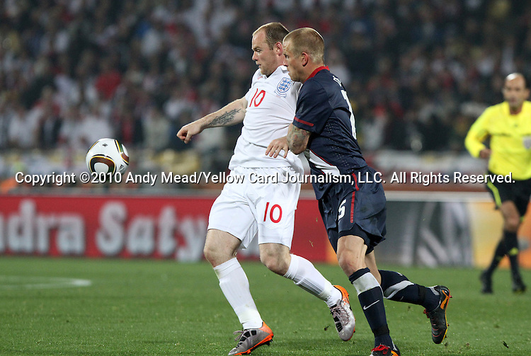 12 JUN 2010: Wayne Rooney (ENG) (10) and Jay DeMerit (USA) (15). The England National Team played the United States National Team to a 1-1 tie at Royal Bafokeng Stadium in Rustenburg, South Africa in a 2010 FIFA World Cup Group C match.