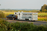 Black Chevy towing horse trailer on country road