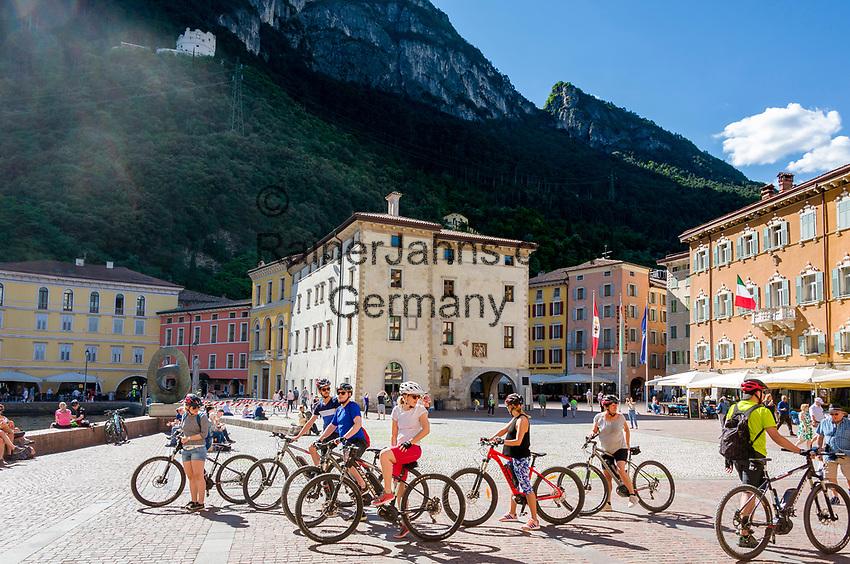 Italy, Trentino, Riva del Garda: popular holiday resort at Lake Garda (Lago di Garda), cyclists at Piazza Tre Novembre | Italien, Trentino, Riva del Garda: beliebter Urlaubsort am Nordufer des Gardasees, Radfahrer auf der Piazza Tre Novembre