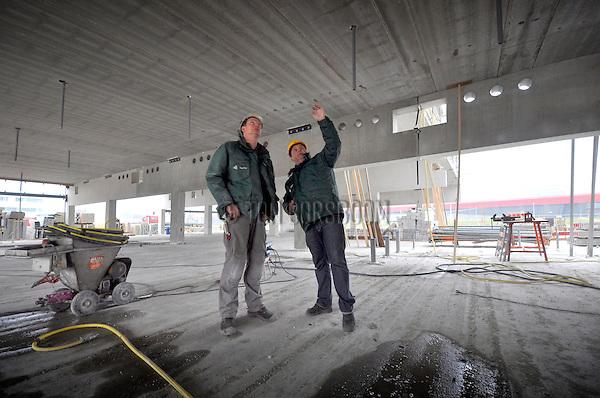 UTRECHT - Achter de bekende rode geluidsmuur langs de snelweg A2 bij Utrecht overlegt de uitvoerder van de Hurks groep over bouw van het nieuwe St. Antonius Ziekenhuis. Bij de bouw van het 83.000 m2 complex zijn Hurks van der linden, Hurks bouw zuid, Hurks beton, Hurks geveltechniek en Delta zonwering betrokken, terwijl ULC groep uit Utrecht de installatiewerkzaamheden zal uitvoeren. Als het nieuwe ziekenhuis dat vijf verdiepingen groot wordt en ruimte gaat bieden aan 270 bedden, een bovengrondse parkeergarage voor ruim 500 auto's en een medisch psychiatrisch centrum in 2013 klaar is, worden de huidige ruim veertig jaar oude ziekenhuizen Overvecht en Oudenrijn gesloten. COPYRIGHT TON BORSBOOM
