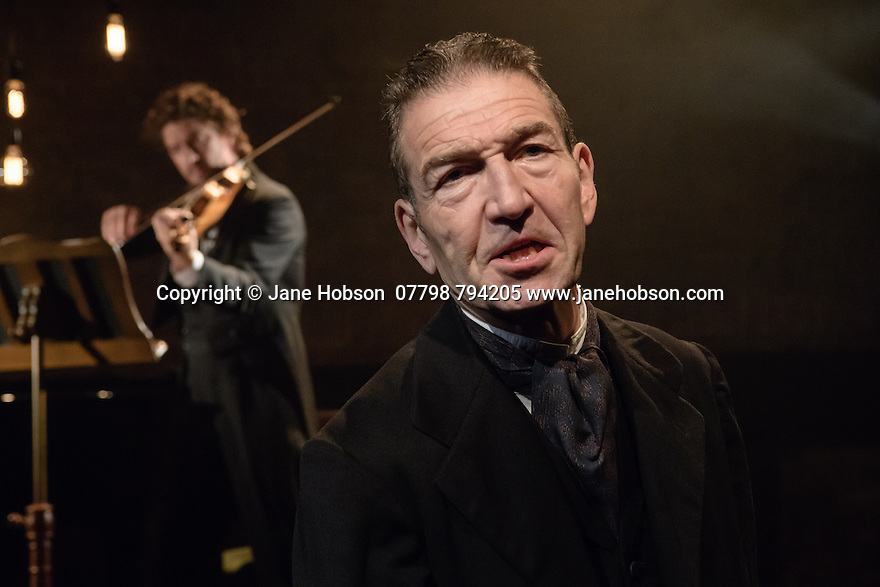 London, UK. 11.07.2016. The Arcola Theatre presents The Theatre Chipping Norton's production of THE KREUTZER SONATA, by Leo Tolstoy, adapted by Nancy Harris. Directed by John Terry, with lighting design by Alexndra Stafford and set and costume design by Alex Berry. Greg Hicks stars as Pozdnyshev. Picture shows: Greg Hicks (Pozdnyshev), Phillip Granell (Violin). Photograph © Jane Hobson.