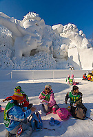 Sapporo, Japan<br /> Sapporo Snow Festival, Odori Park, schoool children sharing lunch in front of large ice sculpted cartoon characters