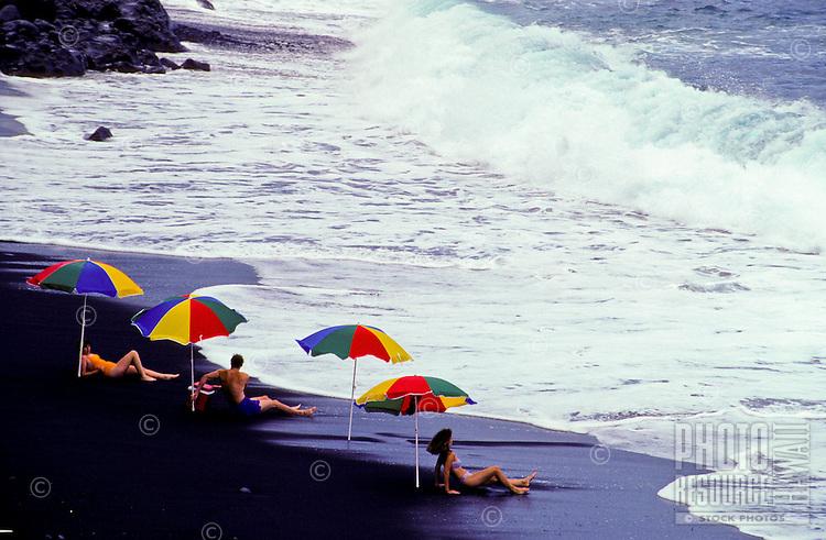 People sunbathe under multicolored umbrellas on the black sand beach at Kehena on the Big Island of Hawaii.