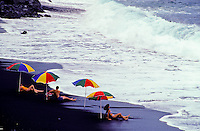 People sunbathe under multicolored umbrellas on the black sand beach at Kehena on the Big Island of Hawaii.
