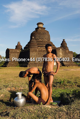 Mrauk U Myanmar (Burma) 2008. Young men washing late afternoon in background Lay Mye Thna Temple.