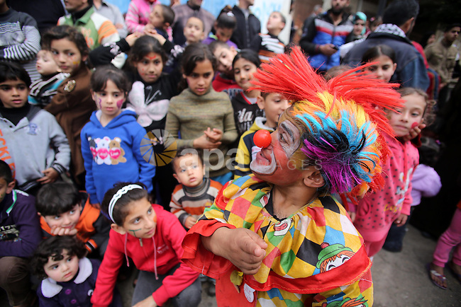 A clown performs in front of Palestinian children during a street game organised by volunteers of the Friday of Joy Initiative, in al-Shati refugee camp, in Gaza city, February 6, 2015. Ten Palestinian volunteers organise street games, painting and drama, every Friday afternoon in the streets of  refugee camps and provide outlets for the children's energy with organised games, dancing and singing, which gives extra psycho-social support to vulnerable children. Photo by Khaled al-Sabbah