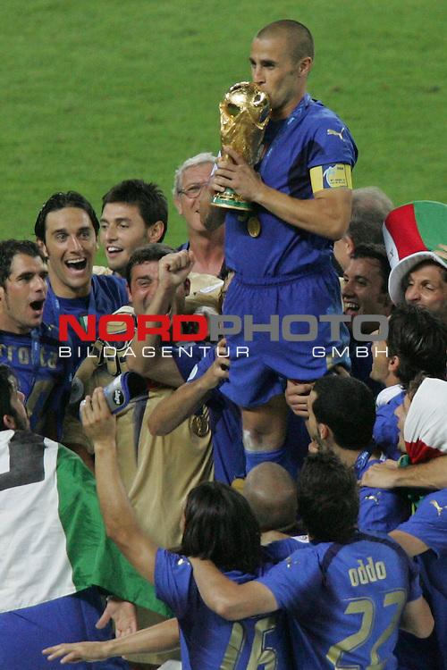 FIFA WM 2006 -  Final - Finale<br /> Play    #64  (09. Juli ) Italien - Frankreich 5:3 n. E. <br /> <br /> Fabio Cannavaro (Mitte) von Italien steht bei der Siegerehrung auf dem Podest und k&uuml;sst den Pokal.<br /> <br /> Foto &copy; nordphoto