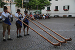 Italy, Dolomites.  <br /> Musicians playing alpenhorns, Castelrotto, Italy. Strong diagonal lines lead viewers into the photo. Also, a nice, descriptive background.