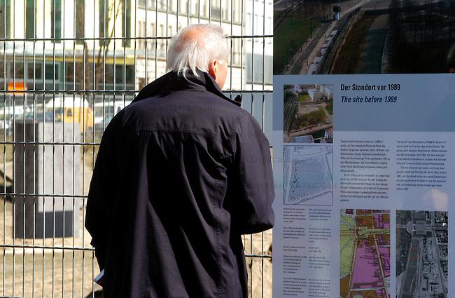 Erste Stelen auf dem Gelaende des geplanten Holocaustmahnmals in Berlin<br /> Am Donnerstag den 3. April 2003 wurden die ersten zwei Stelen auf das Gelaende des geplanten Holocaustmahnmals in Berlin gesetzt. Ab August 2003 soll dann mit dem Bau des Mahnmals begonnen werden.<br /> Die Fertigstellung des Mahnmals sollte zuerst im Jahr 2004 sein, nun ist das Jahr 2005 im Gspraech.<br /> Hier: Ein Tourist betrachtet eine Schautafel am Bauzaun des Mahnmal-Gelaendes, im Hintergrund die Stelen.<br /> 4.4.2003, Berlin<br /> Copyright: Christian-Ditsch.de<br /> [Inhaltsveraendernde Manipulation des Fotos nur nach ausdruecklicher Genehmigung des Fotografen. Vereinbarungen ueber Abtretung von Persoenlichkeitsrechten/Model Release der abgebildeten Person/Personen liegen nicht vor. NO MODEL RELEASE! Nur fuer Redaktionelle Zwecke. Don't publish without copyright Christian-Ditsch.de, Veroeffentlichung nur mit Fotografennennung, sowie gegen Honorar, MwSt. und Beleg. Konto: I N G - D i B a, IBAN DE58500105175400192269, BIC INGDDEFFXXX, Kontakt: post@christian-ditsch.de<br /> Bei der Bearbeitung der Dateiinformationen darf die Urheberkennzeichnung in den EXIF- und  IPTC-Daten nicht entfernt werden, diese sind in digitalen Medien nach &sect;95c UrhG rechtlich geschuetzt. Der Urhebervermerk wird gemaess &sect;13 UrhG verlangt.]