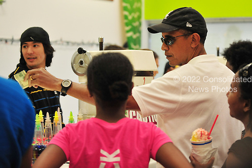 United States President Barack Obama pays with a hundred dollar bill at Island Snow in Kailua, Hawaii, Monday, January 3, 2011. The first family is wrapping up their vacation in Hawaii today.  .Credit: Cory Lum / Pool via CNP