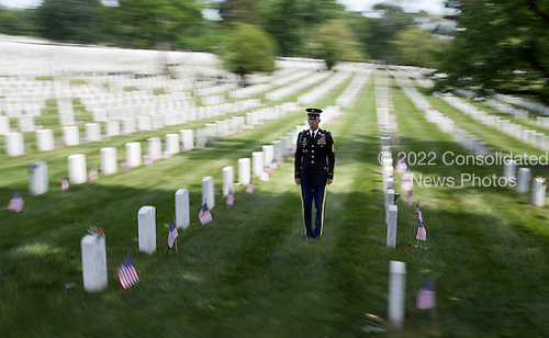 A member of the honor guard stands at attention as the motorcade with United States President Barack Obama passes during Memorial Day activities at Arlington National Cemetery in Washington on Monday, May 27, 2013. .Credit: Joshua Roberts / Pool via CNP