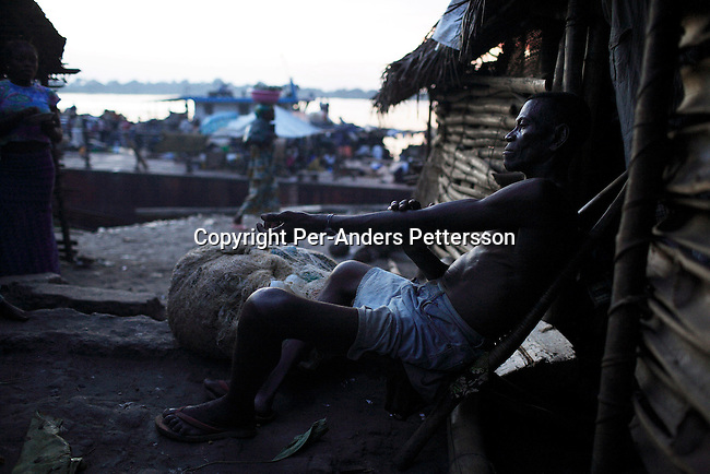 MBANDAKA, DEMOCRATIC REPUBLIC OF CONGO APRIL 14: Tabo Evariste, age 58, relaxes outside his house on April 14, 2006 in the port in Mbandaka, Congo, DRC. Mr. Evariste is a fisherman, and started fishing with his father when he was two years old. The port is a big trading point, and about 700 kilometers from the capital Kinshasa. Many villagers come here to trade goods. The Congo River is a lifeline for millions of people, who depend on it for transport and trade. Congo is planning to hold general elections by July 2006, the first democratic elections in forty years. (Photo by Per-Anders Pettersson)..