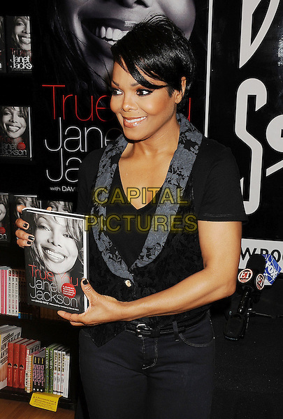 "JANET JACKSON.Janet Jackson Book Signing for ""TRUE YOU: A Guide To Finding And Loving Yourself"" held at Book Soup, West Hollywood, California, USA, .15th April 2011..half length grey gray  black  t-shirt waistcoat    smiling holding book .CAP/ROT/TM.© TM/Roth/Capital Pictures"