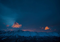 Last rays of light catch clouds over the Chugach Mountains.