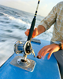 USA, Florida, man sitting on fishing boat preparing to reel in a fish, Destin