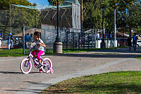 A girl rides her bicycle down the paver pathway at South Gate Park while two people walk behind her in the shade as baseball players play on the field.