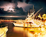 USA, Florida, boats in marina with an approaching storm at night, Islamorada