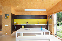 The open plan kitchen and dining area has a signature wall of bright yellow