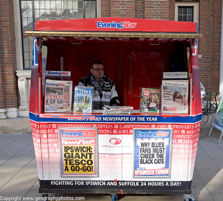 Local newspaper seller in street booth, Ipswich, Suffolk, England