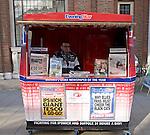Local newspaper seller in street booth, Ipswich, Suffolk, England