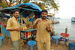 Two indan man in the harbour of Fort Cochin having a sweet tea and biscuit at one of the typical small mobile tea shops, Fort Cochin (Kochi), Kerala.