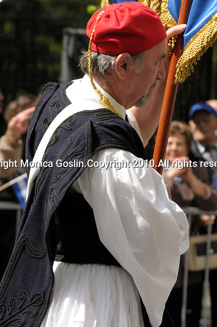 Greek Parade in New York City. An older man holding a flag and dressed in traditional clothing, walks in the Greek Parade in New York City.