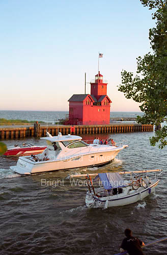 Pleasure crafts glides by the red lighthouse near the Holland Michigan Harbor in the evening