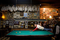 "Local men enjoy a beer and games of billiards of chess at Cafe de Garcia in Buenos Aires'  Villa Devoto neighborhood. Garcia, opened in 1937 by the Garcia family, wears its past on its ""sleeves."" A Boca Junior T-shirt signed by Diego Maradona joins accordions, cue sticks, wine skins, rifles, and numerous vintage items on shelves and yellowed walls. (Kevin Moloney for the New York Times)"