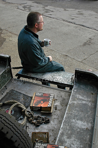 Car mechanic having a morning break on the loadbed of a 1950's Land Rover Series One truck. --- No releases available. Automotive trademarks are the property of the trademark holder, authorization may be needed for some uses.
