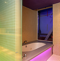 Every 15 seconds the lighting beyond the large window in this bathroom changes from red to purple to blue to green