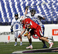 Max Schmidt (9) of Maryland has the ball checked away from him by David Lawson (31) of Duke during the Face-Off Classic in at M&T Stadium in Baltimore, MD