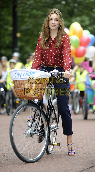 Kelly Brook.Kelly Brook photocall to launch this year's Skyride Event, London, England.September 4th, 2011.full length bike bicycle blue trousers red blouse print basket sitting.CAP/DH.©David Hitchens/Capital Pictures.