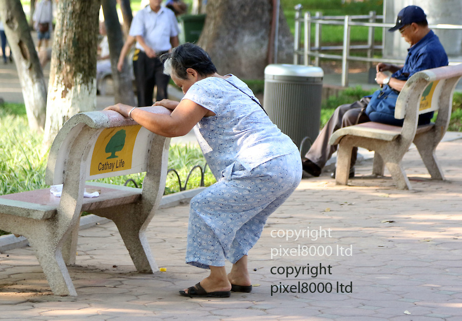 """Pic shows: Elderly people early morning workouts in Hanoi, Vietnam. <br /> <br /> Woman uses bench to stretch herself. Many people use the benches, trees and whatever else is around as makeshift gym equipment<br /> <br /> <br /> Every morning starting as early as 5.a.m  hundreds of OAPS flock to the Hoan Kiem  (Lake of the Restored Sword) Lake in the centre of town.<br /> <br /> Unlike their Western counterparts who might be having breakfast and watchingTV they come to keep fit in various ways.<br /> <br /> Exercising daily into their 80's and even 90's the North Vietnamese partake in yoga, tai chi, dancing, badminton, weights and stretching exercises beside the picturesque<br /> lake.<br /> <br /> 89 year old """"Mr Kim"""" sporting dark glasses and a traditional North Vietnamese pith helmet said """"I was a soldier in the war. I am used to keeping myself fit. <br /> <br /> """"I come very early most mornings. It is too hot to sleep anyway at this time of the year. I can't afford air conditioning.<br /> <br /> """"My back hurts a bit so I take it easy. I just do a few yoga stretching exercises on this bench to keep myself supple.<br /> <br /> """"It's also a lovely place to meet friends and share a cup of green tea and maybe packet of biscuits.""""<br /> <br /> <br /> <br /> <br /> <br /> <br /> Pic by Gavin Rodgers/Pixel 8000 Ltd"""