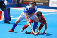 Alan Forsyth of Scotland shields the ball from Jinkang Rim of Korea during the Hockey World League 9th and 10th placing match between Korea and Scotland at the Olympic Park, London, England on 22 June 2017. Photo by Steve McCarthy.
