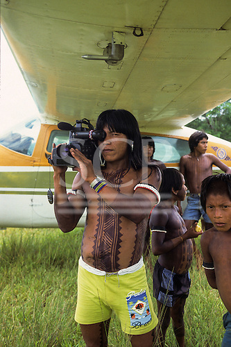 A-Ukre Village, Xingu, Brazil. Kimabaiti, a Kayapo man, using a Panasonic video camera under the wing of an airplane. Photograph from 1989.