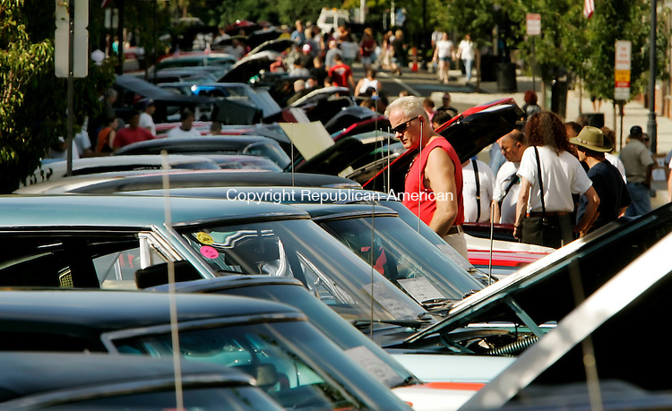 NAUGATUCK, CT - 05 AUGUST 2005 -080605JS02-- Mark Tonges of Naugatuck looks over cars during the second  annual Naugatuck Classic Car Show held Saturday in downtown Naugatuck  --Jim Shannon Photo--Cathy Davis, Anne Butler,  Naugatuck are CQ