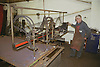 Man cutting shapes using machine at engineering works,