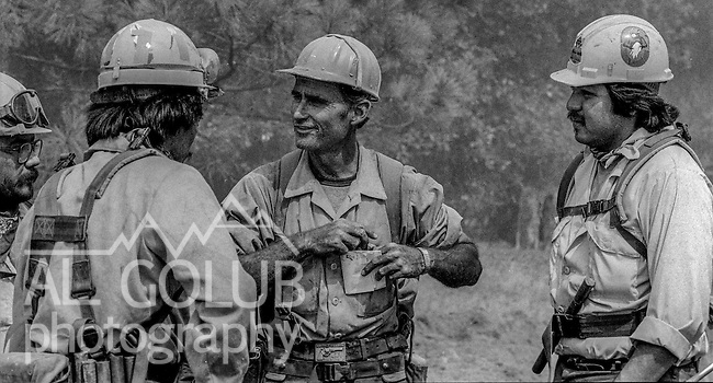 September 1, 1987 Buck Meadows, California – Stanislaus Complex Fire -- Bulldozer driver Johnson talks with firefighters in fire camp while waiting for next fireline assignment.  The Stanislaus Complex Fire consumed 28 structures and 145,980 acres.  One US Forest Service firefighter, David Ross Erickson, died from a tree-felling accident.