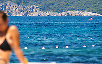 View over the deep blue sea and white buoys, young shapely woman out of focus, sitting in the foreground clad in bikini. Uvala Sumartin bay between Babin Kuk and Lapad peninsulas. Dubrovnik, new city. Dalmatian Coast, Croatia, Europe.